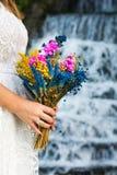 Jeune mariée tenant le bouquet de mariage devant une cascade Photo libre de droits