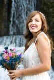 Jeune mariée tenant le bouquet de mariage devant une cascade Photographie stock libre de droits