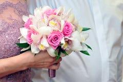 Jeune mariée tenant le bouquet de roses rouges Photographie stock