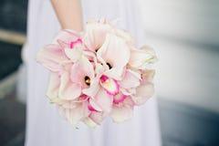 Jeune mariée tenant le bouquet des zantedeschias Image stock