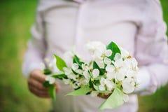 Jeune mariée tenant le bouquet du pommier de fleur le jour du mariage, Photos stock