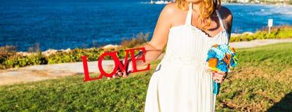 Jeune mariée tenant le bouquet et l'amour de mot Image libre de droits