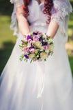 Jeune mariée tenant le bouquet lilas de mariage Photos libres de droits