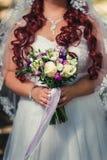 Jeune mariée tenant le bouquet lilas de mariage Photo stock
