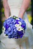 Jeune mariée tenant le bouquet lilas de mariage Image stock