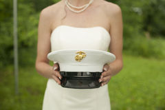 Jeune mariée tenant le chapeau de l'armée de son mari Photos libres de droits