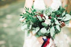Jeune mariée tenant le grand et beau bouquet de mariage avec des fleurs Photo libre de droits