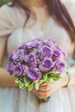 Jeune mariée tenant son bouquet des roses pourpres Image libre de droits