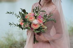 Jeune mariée tenant un beau bouquet nuptiale Bouquet de mariage des roses de pêche par David Austin, aqua tête simple de rose de  Photo libre de droits