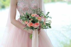 Jeune mariée tenant un beau bouquet nuptiale Bouquet de mariage des roses de pêche par David Austin, aqua tête simple de rose de  Photographie stock libre de droits