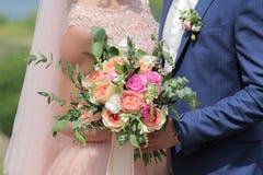 Jeune mariée tenant un beau bouquet nuptiale Bouquet de mariage des roses de pêche par David Austin, aqua tête simple de rose de  Photo stock