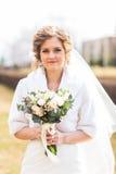 Jeune mariée tenant un bouquet de mariage d'hiver photo stock