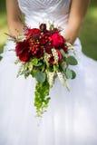 Jeune mariée tenant un bouquet des fleurs Photos stock