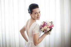 Jeune mariée tenant un bouquet des roses Photos libres de droits