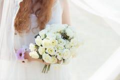 Jeune mariée tenant un groupe de roses blanches Photographie stock