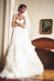 Jeune mariée tendre dans la robe de mariage posant sur le lit de fond Image stock