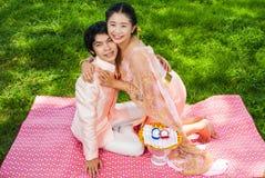 Jeune mariée thaïlandaise asiatique embrassant son marié mignon Images stock