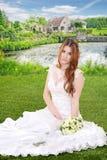 Jeune mariée avec le bouquet se reposant par le lac Photos libres de droits