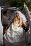 Jeune mariée dans la robe de mariage descendant du véhicule Image stock