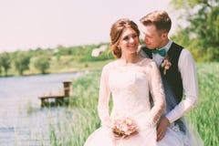 Jeune mariée de flirt avec le marié près de l'étang Photographie stock