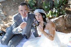 Jeune mariée de marié s'asseyant faisant des bulles de savon extérieures Photos libres de droits