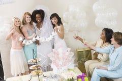 Jeune mariée et amis tenant le mariage Bells avec des femmes grillant Champagne Photo stock