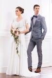 Jeune mariée magnifique avec un petit bouquet et un marié beau dans le rétro intérieur Image stock