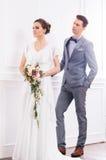 Jeune mariée magnifique avec un petit bouquet et un marié beau dans le rétro intérieur Photo libre de droits