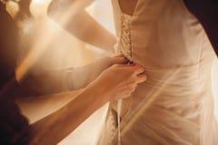 Jeune mariée mettant sur la robe de mariage Photos stock