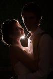 Jeune mariée regardant son mari avec une lumière derrière Image stock