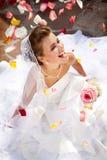 Jeune mariée riante heureuse s'asseyant dehors sur le plancher avec des pétales Images libres de droits