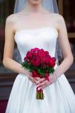 Jeune mariée tenant un bouquet de mariage des roses rouges Photographie stock libre de droits