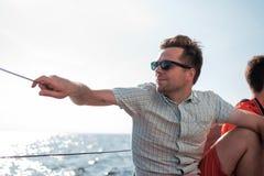 Jeune marin caucasien détendant heureusement sur le yacht de voilier Il loooks de côté et rêve Images libres de droits