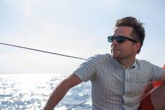 Jeune marin caucasien détendant heureusement sur le yacht de voilier Il loooks de côté et rêve Images stock
