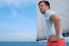 Jeune marin caucasien détendant heureusement sur le yacht de voilier Il loooks de côté et rêve Photographie stock