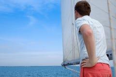 Jeune marin caucasien détendant heureusement sur le yacht de voilier Il loooks de côté et rêve Photos libres de droits