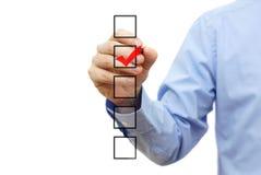 Jeune marque de vérification d'homme d'affaires sur la liste de contrôle avec le marqueur Photographie stock libre de droits