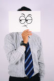 Jeune masque de doute de Wearing d'homme d'affaires d'isolement sur le blanc Photographie stock