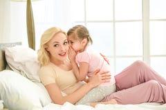 Jeune matin de mère et de fille sur le lit à l'intérieur Photos stock
