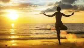 Jeune méditation de silhouette de femme de yoga sur la plage au coucher du soleil nature Images stock