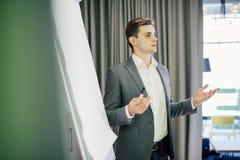 Jeune meneur d'équipe ou directeur sûr se tenant devant un tableau de conférence et un présent projet sur le bureau images stock