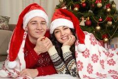 Jeune mensonge de couples dans la décoration de Noël Intérieur de maison avec les cadeaux et l'arbre de sapin Concept de vacances Photos stock