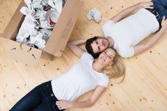 Jeune mensonge fatigué de couples tête à tête sur le plancher images stock