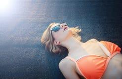 Jeune mensonge femelle et prendre un bain de soleil sur le modèle bleu-foncé Jour, extérieur images stock