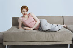 Jeune mensonge femelle sur Sofa At Home Photo stock