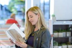 Jeune menu blond de lecture de femme photographie stock libre de droits
