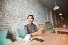 Jeune message textuel femelle magnifique d'écriture sur le pavé tactile tout en se reposant dans l'intérieur de café Photos stock