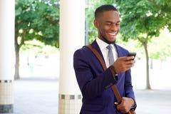 Jeune message textuel heureux de lecture d'homme d'affaires à son téléphone portable image libre de droits