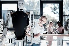 Jeune mignon obtenant excité tout en embrassant la machine robotique Photographie stock libre de droits