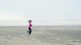 Jeune, mince fille dans un T-shirt rose et courses noires de guêtres le long d'une plage sablonneuse abandonnée Formation extérie clips vidéos